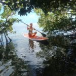 Blond haired girl in a bikini sitting crossed legged on a paddleboard in a mangrove cave