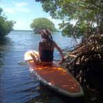 woman sitting on a paddleboard in the mangroves of the Florida Keys
