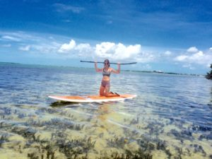 Girl kneeling on a paddlebard with paddle raised up behind her head