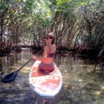 Girl kneeling on a paddlebard, paddling into the mangroves