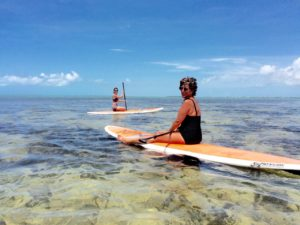 Mother and daughter sitting on paddle boards in the Florida Keys on a Keys Boat Tours Motor Paddleboard combo tour
