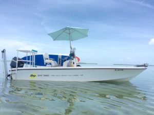 Keys Boat Tours motor boat at anchor with paddleboards and light blu umbrella